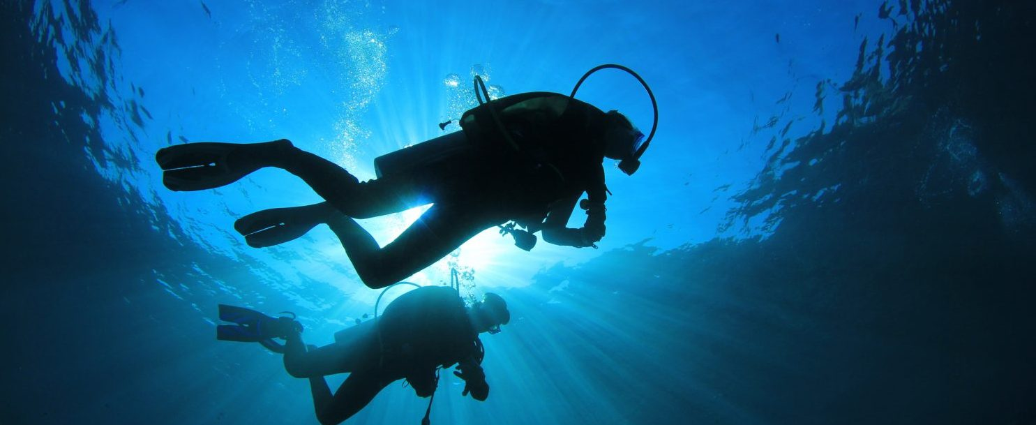 Two scuba divers silhouetted against the sun while they are diving the florida panhandle