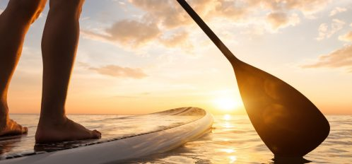 Stand up paddle boarding on a quiet sea with warm summer sunset colors, close-up of legs of girl on 30A paddle board rentals adventure