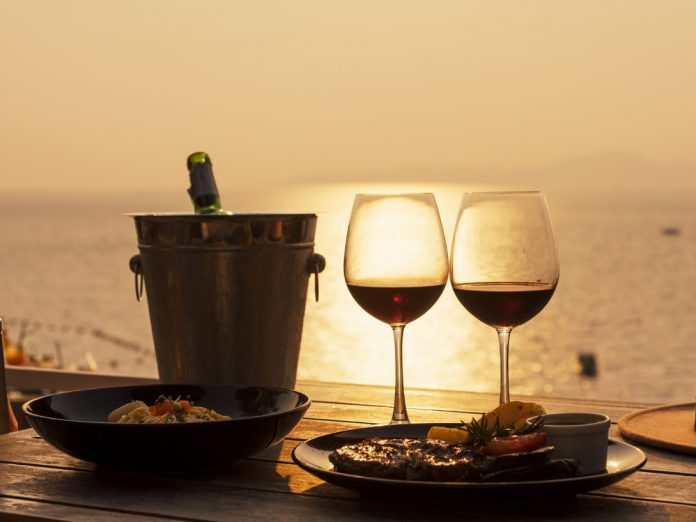 View of wine glasses in front of a sunset showing the best of Sandestin dining