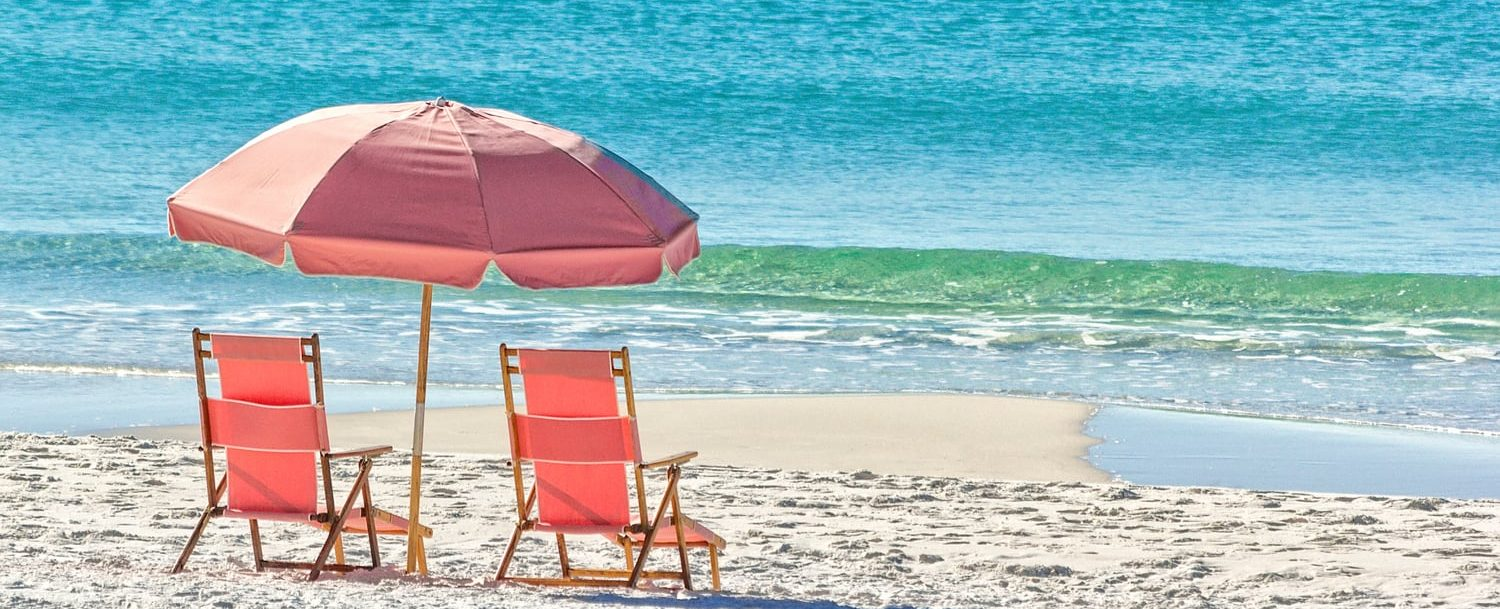 Beach chairs and umbrella by the water on a white sand beach | Blue Mountain Beach Weather
