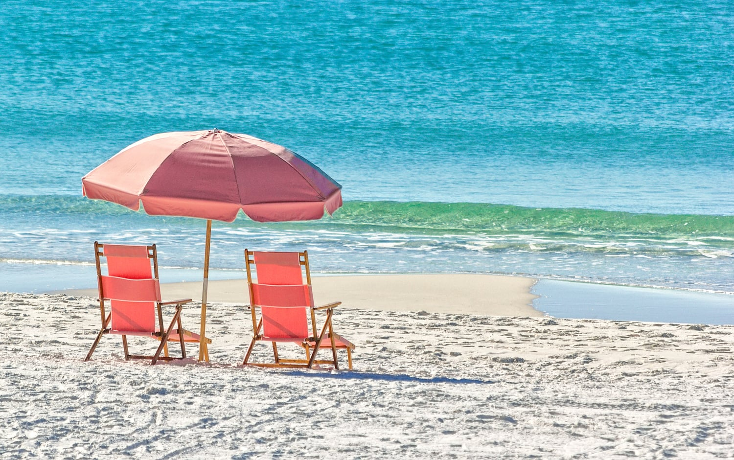 Beach chairs and umbrella by the water on a white sand beach |