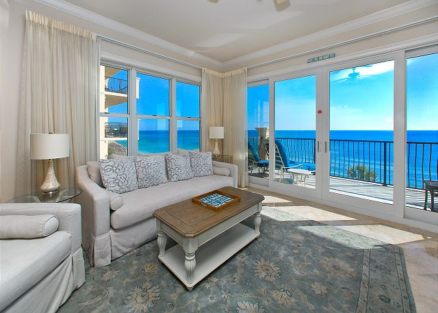 View of the living room with white, modern furniture - balcony in the backdrop overlooking the ocean