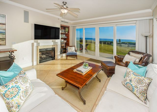View of the living room with flat screen tv, white couch and ocean view