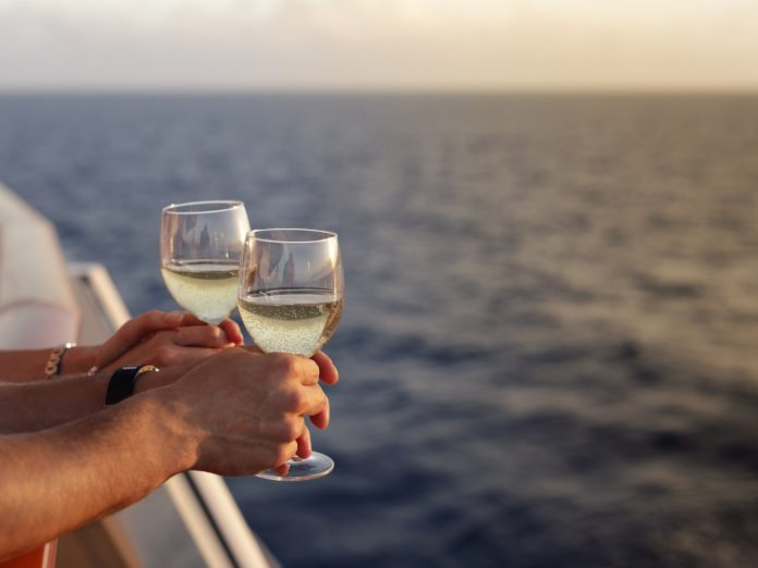 Close up of couple's hands on a sunset cruise with drinks with ocean in the background