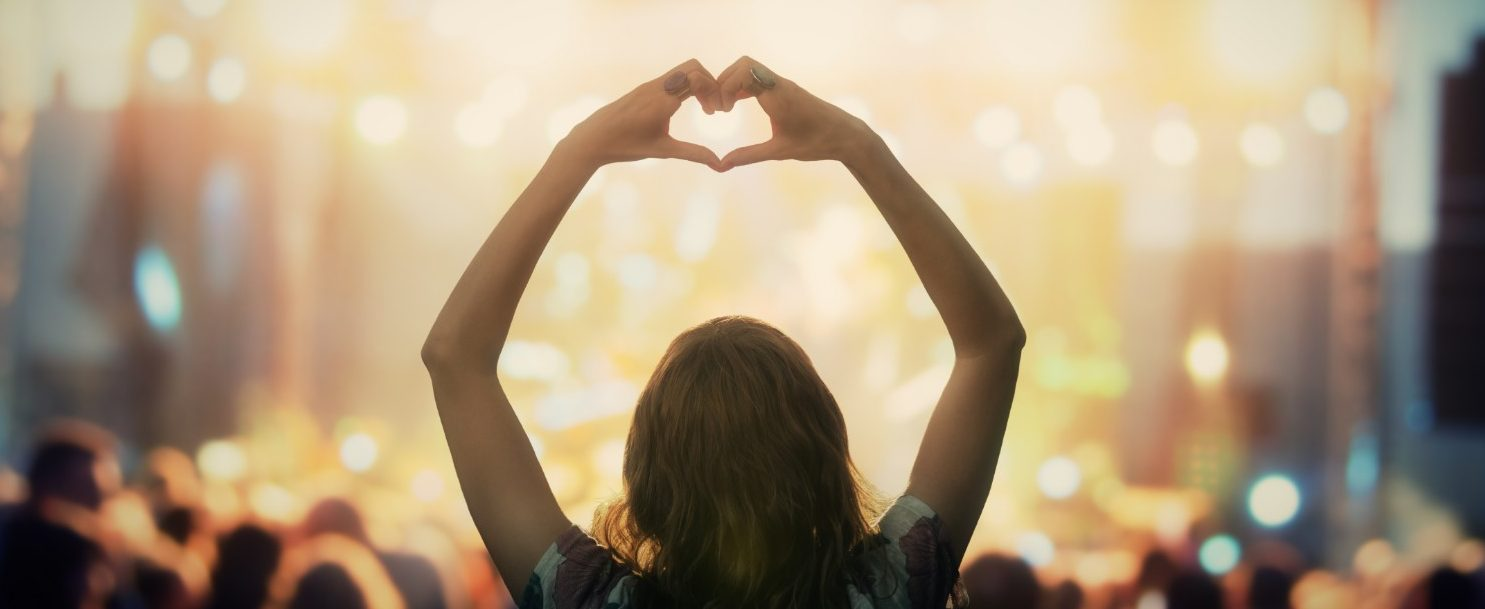 Girl attending a concert at Gulf Coast Jam while signing a heart with her hands