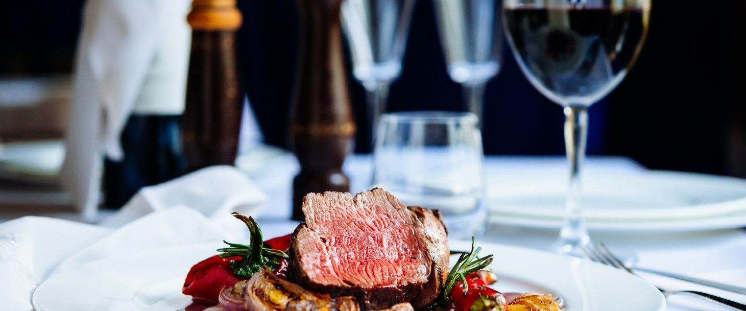 Beef steak with grilled vegetables served on white plate | Best Restaurants in Sandestin