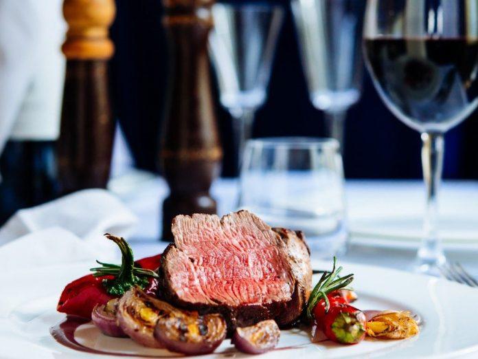 Beef steak with grilled vegetables served on white plate | Best Restaurants in Sandestin