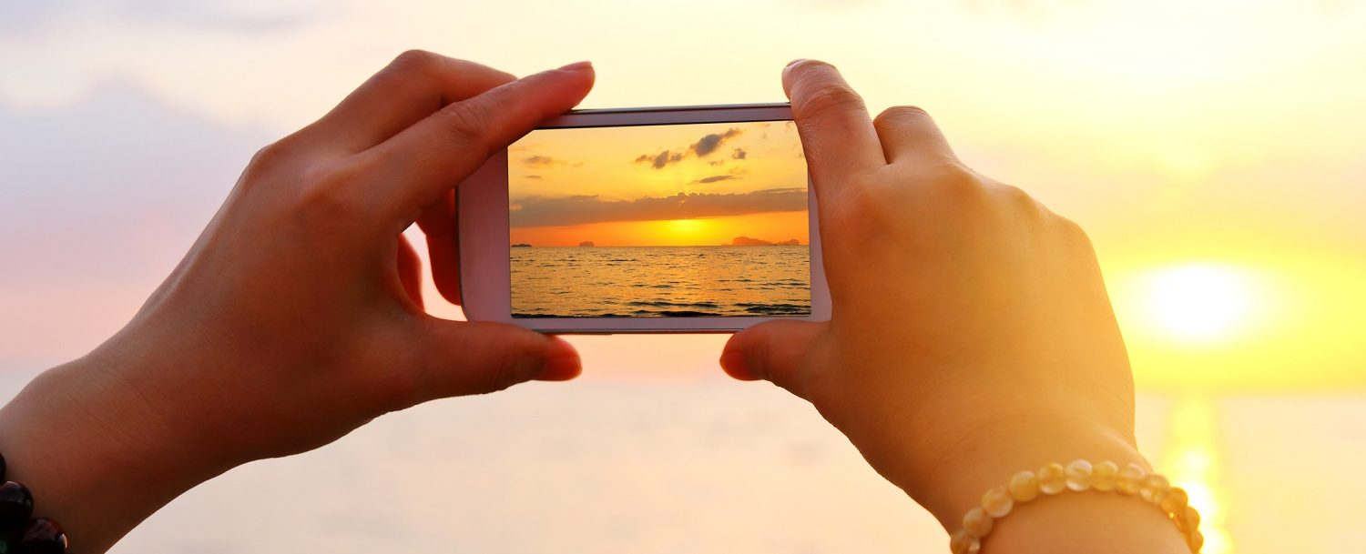 Hand with phone taking picture of sunrise | Spots for 30A Selfies