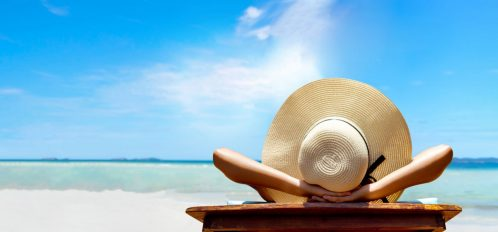 Woman with a hat tanning on a beach | Florida Panhandle Weather in July